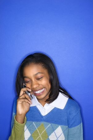 Portrait of African-American teen girl talking on cellphone smiling standing in front of blue background. photo
