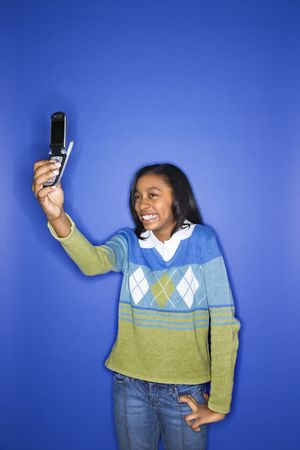 Portrait of African-American teen girl taking photo with camera phone standing in front of blue background. Stock Photo - 2376523