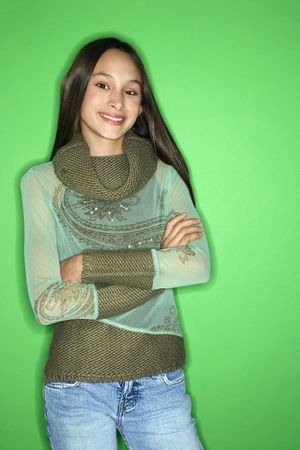 Portrait of smiling Asian-American teen girl with arms crossed standing in front of green background. Stock Photo - 2376574