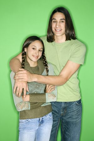 Portrait of Asian-American girl and teen boy standing with arms around eachother smiling against green background. photo