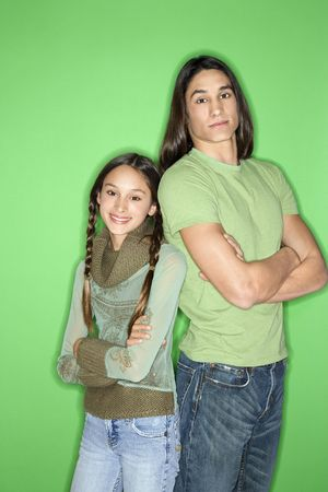 Portrait of Asian-American girl and teen boy standing back to back against green background. Stock Photo - 2376549