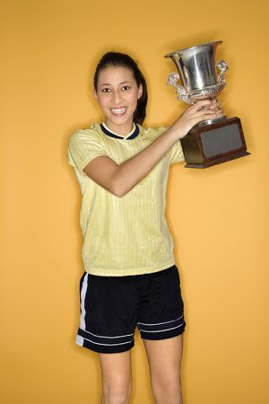 victor: Portrait of Multi-racial teen girl in soccer uniform holding trophy and smiling standing against yellow background.