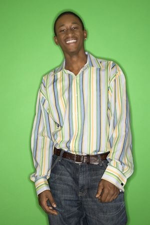 only one teenage boy: Portrait of smiling African-American teen boy standing in front of green background.