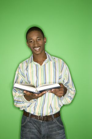 only one teenage boy: Smiling African-American teen boy holding a book. Stock Photo