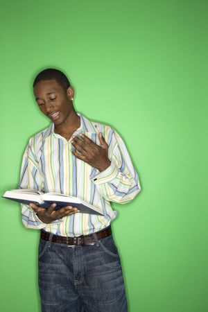 only one teenage boy: Portrait of African-American teen boy reading book standing in front of green background.
