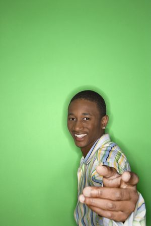 only one teenage boy: Portrait of smiling African-American teen boy holding hand out toward viewer against green background.