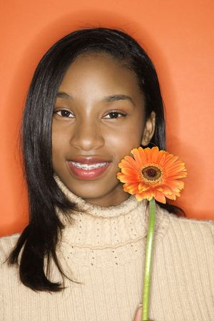 Portrait of smiling African-American teen girl holding single Gerbera Daisy against orange background. photo