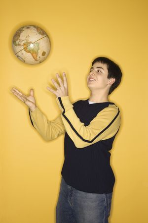 careless: Portrait of smiling Caucasian teen boy tossing globe in air standing against yellow background.