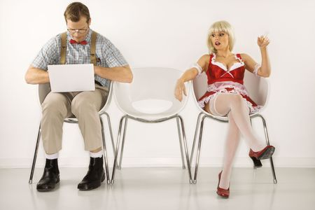 french maid: Caucasian young man dressed like nerd sitting with laptop with Caucasian young blonde woman looking at him. Stock Photo