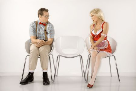 suspender: Caucasian young man dressed like nerd and Caucasian young blonde woman in french maid outfit sitting and looking at eachother.