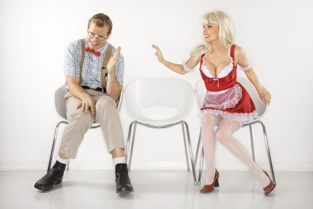 Young blonde woman flirting with shy Caucasian young male nerd.