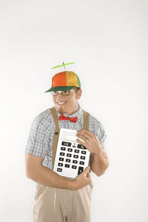 beanie: Caucasian young man dressed like nerd wearing beanie and smiling while holding large calculator.
