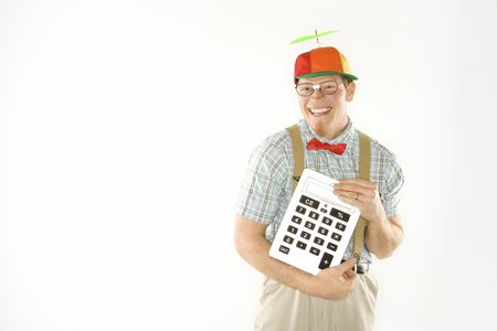 dunce cap: Caucasian young man dressed like nerd wearing beanie and smiling while holding large calculator.