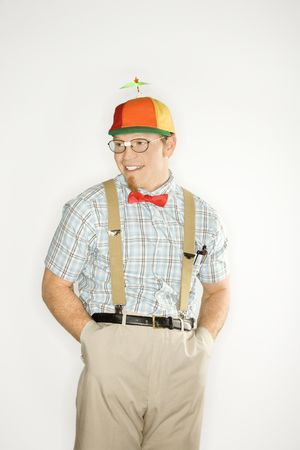 dweeb: Caucasian young man dressed like nerd wearing propeller cap with hands in pockets.