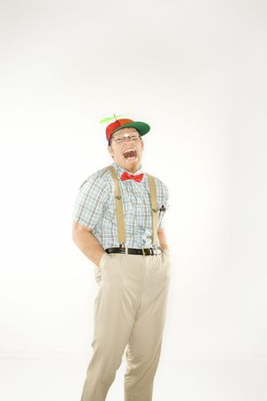 dweeb: Caucasian young man dressed like nerd wearing propeller cap with hands in pockets looking at viewer with mouth open.