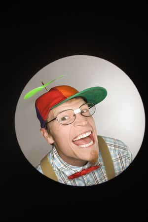 dweeb: Close up circle vignette of Caucasian young man dressed like nerd wearing propeller cap with mischievous look.