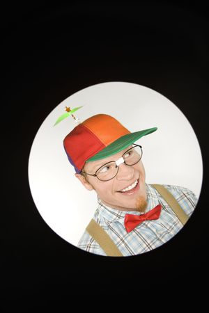 dweeb: Close up circle vignett of Caucasian young man dressed like nerd wearing propeller hat looking mischievous. Stock Photo