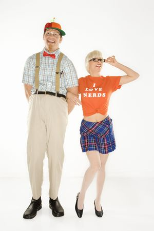 dweeb: Caucasian young man dressed like nerd wearing propeller hat with blonde Caucasian young woman in nerdy eyeglasses and tshirt reading I love nerds and plaid skirt.