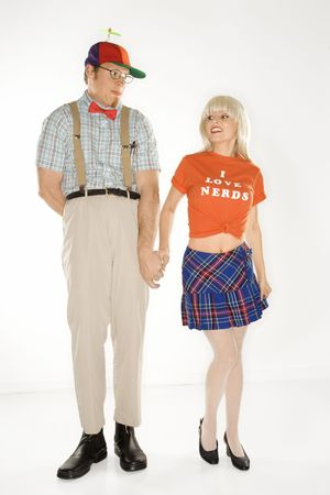 dweeb: Caucasian young man dressed like nerd wearing propeller hat holding hands with Caucasian blonde young woman wearing tshirt reading I love nerds and plaid skirt. Stock Photo