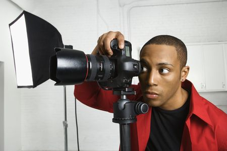 human photography: African American young male adult looking through camera on tripod.