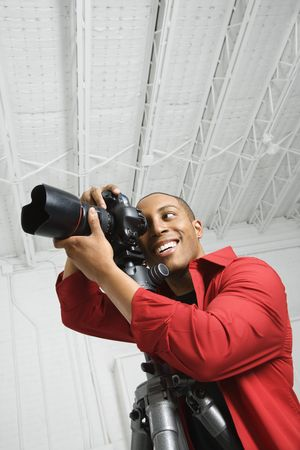 African American young male adult looking through camera on tripod. photo