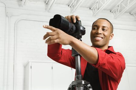photographers: African American young male adult with camera and pointing.