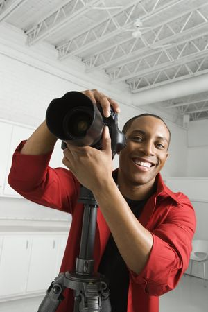 African American young male adult with camera on tripod looking at viewer smiling. photo