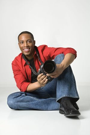 African American young male adult sitting on floor with camera looking at viewer smiling. Stock Photo - 2376280