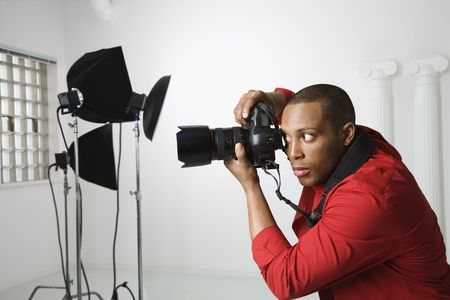 art studio: African American young male adult photographing in studio.