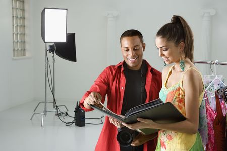 human photography: African American young male adult photographer and young adult female model looking at portfolio. Stock Photo