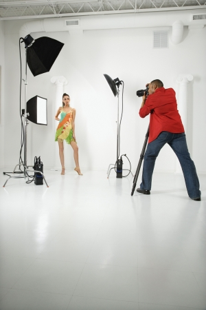 human photography: Young adult female Caucasian model being photographed in studio by young adult African American male photographer.