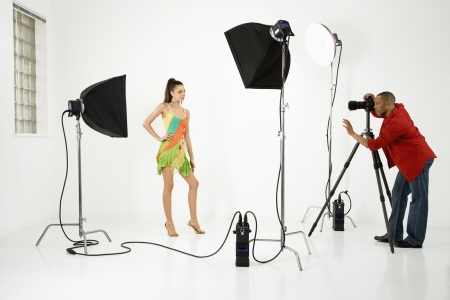 studio shoot: Young adult female Caucasian model being photographed in studio by young adult African American male photographer.