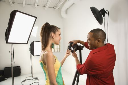 working model: Young African American male adult and Caucasian young female adult previewing image on digital camera.