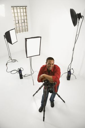 Young African American male adult photographer posing in studio. photo