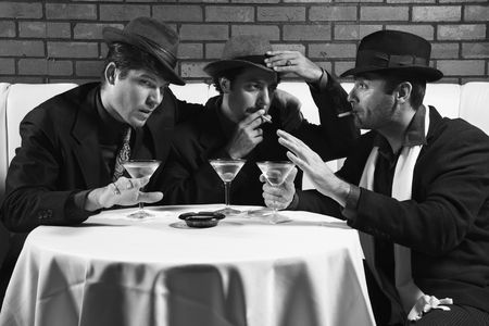 Three Caucasian prime adult males in retro suits sitting at table drinking and smoking and talking. photo