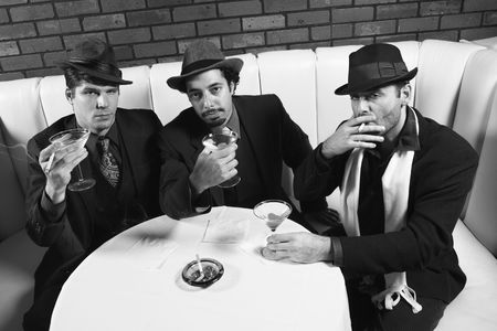 prime adult: Three Caucasian prime adult males in retro suits sitting at table with cocktails looking at viewer.