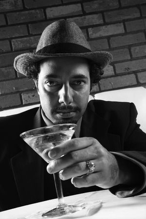 prime adult: Caucasian prime adult male in retro suit sitting at table with martini looking at viewer.