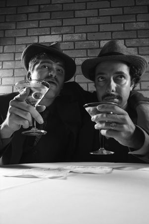 prime adult: Two Caucasian prime adult males in retro suits sitting at table with martinis.