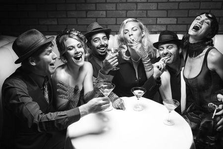 lounge bar: Group of Caucasian prime adult retro males and females sitting at table in lounge laughing. Stock Photo
