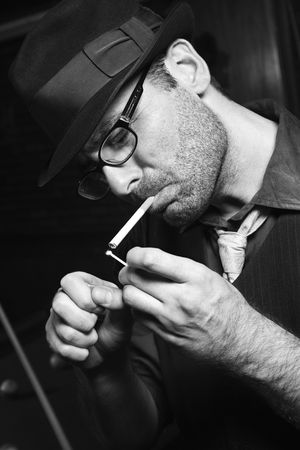 prime adult: Caucasian prime adult retro male lighting cigarette.