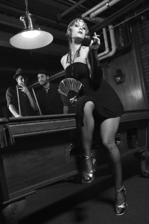 flapper: Caucasian prime adult female standing in front of pool table with two Caucasian prime adult men in background.