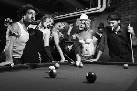 takes: Group of Caucasian prime adult retro males and females trying to distract man as he takes pool shot.