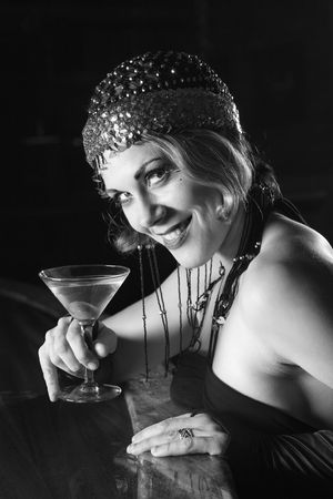 flapper: Caucasian prime adult retro female sitting at bar with martini looking at viewer.