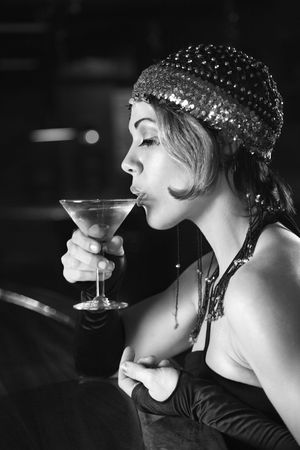 vertical bars: Caucasian prime adult retro female sitting at bar drinking martini.