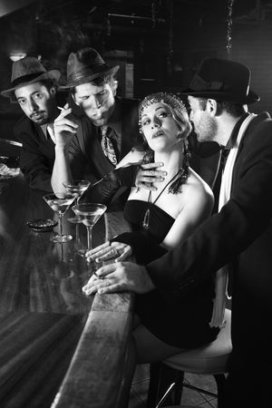 flapper: Caucasian prime adult retro female sitting at bar surrounded by suitors.