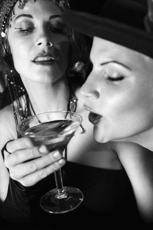 lounge bar: Caucasian prime adult retro female taking drink of girl friends martini.