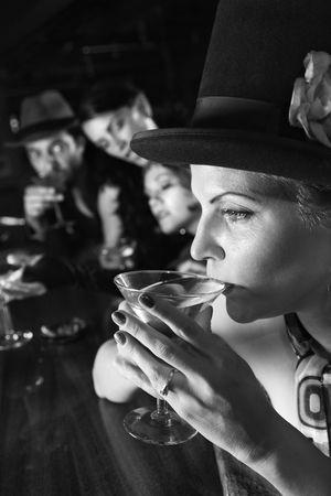 lounge bar: Caucasian prime adult retro female sitting at bar drinking martini.
