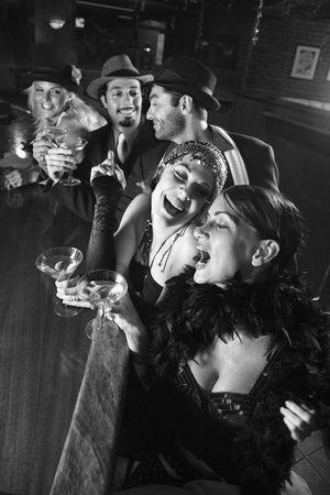 flapper: Adultos de raza cauc�sica prime retro las mujeres y los hombres sentados en la barra.