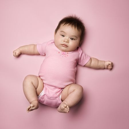 infants: Asian baby lying on back lookin up at viewer with arms out to side.