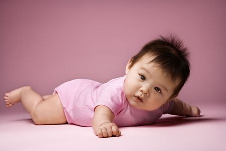 Asian baby lying on stomach looking at viewer holding arms out to side. Stock Photo